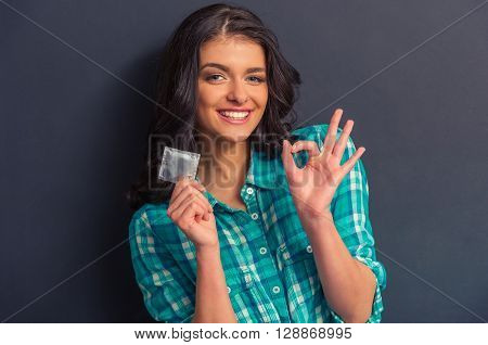 Portrait of attractive girl holding a condom showing Ok sign and smiling against dark background