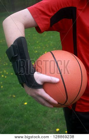 A boy has sprained his wrist from playing basketball.
