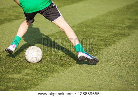 Feet of young players in soccer with a ball close-up. Junior league on soccer