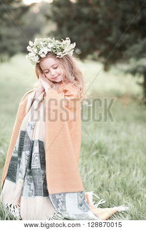 Smiling kid girl wearing flower wreath outdoors. Eyes closed. Childhood.