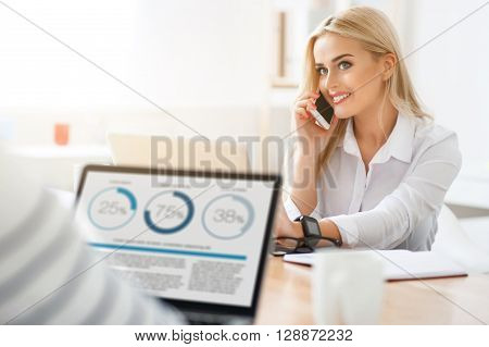 Playful mood.  Positive content charming woman talking on cell phone and expressing gladness  while her colleague sitting at the table