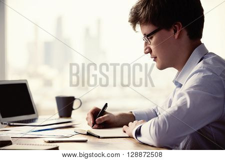 Sideview of caucasian businessman writing something in notepad placed on wooden office desk with laptop smartphone coffee and other items