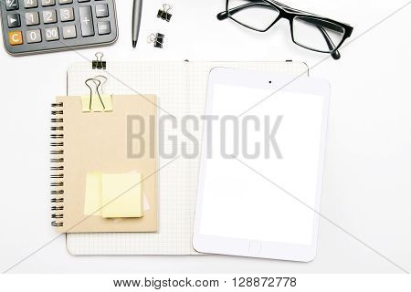 Topview of white desk with blank tablet screen notepad with clips glasses and other items. Mock up