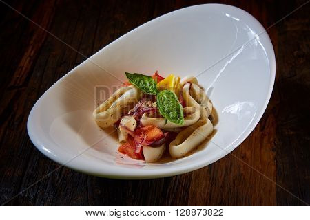 healthy rings squid salad with tomatoes decorated with basil leaves