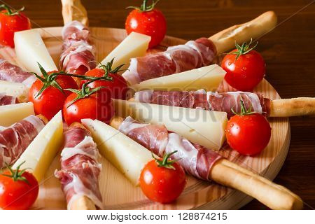 Close up of an Italian chopping board with ham cheese and cherry tomatoes