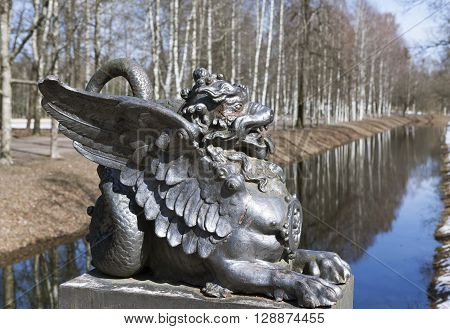 Tsarskoye Selo, Russia -April 16, 2016: Dragon figure with wings, which is set on a granite pedestal. Dragons sit at the base of the bridge. The bridge was built in 1785 designed by architect Cameron.