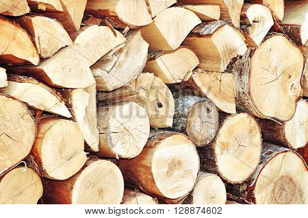 Natural wooden background - closeup of chopped firewood. Firewood stacked and prepared for winter
