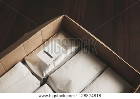 Closeup Opened Big Carton Box Full Of Blank Hermetic White Packages With Coffee Or Tea. Everything O