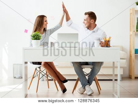 On the edge of delight. Cheerful positive smiling colleagues sitting at the table and giving high five while working in the office
