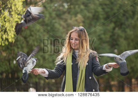 Photo Of Girl And Doves.  Feeding Pigeons In The Park