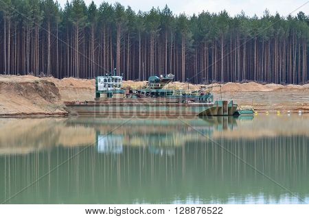 mining of sand bucket boat in the sand quarry, South Bohemia Czech Republic