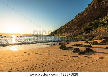 Sunrise in the Beach with Rock and Footsteps in Sand