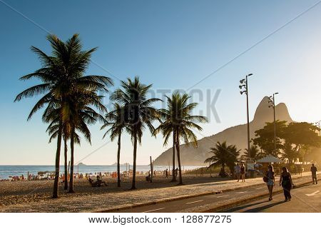 Rio de Janeiro, Brazil - March 27, 2016: People walk along a car-free Avenida Vieira Souto at sunset on Ipanema Beach.