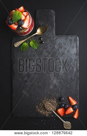 Healthy breakfast food frame. Chia pudding with fresh berries and mint on black slate stone board over dark background. Top view, copy space