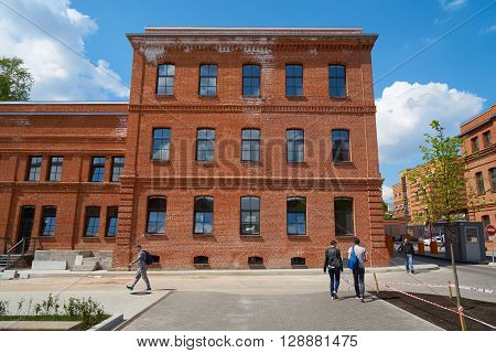Moscow Russia - May 06 2016: View on red brick building of former Arma factory and some pedestrians walking by. Nizhniy Susalniy pereulok (lane) in Moscow.