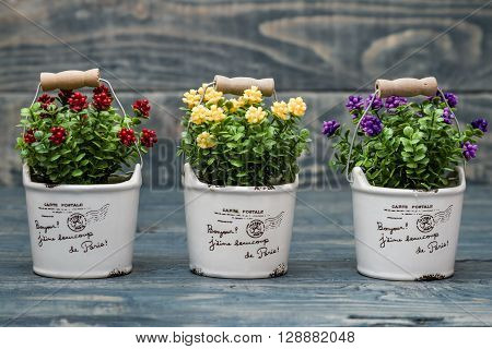 Artificial Yellow, Purple And Red Flowers In A Flowerpot