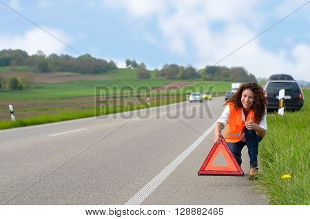Smiling Woman Putting Out A Traffic Warning Sign