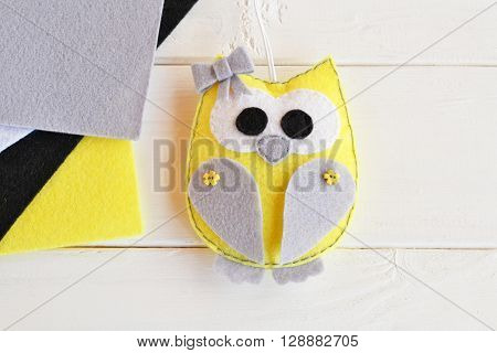 Felt owl toy. Stuffed owl. Grey, yellow, black, white felt. White background. Top view