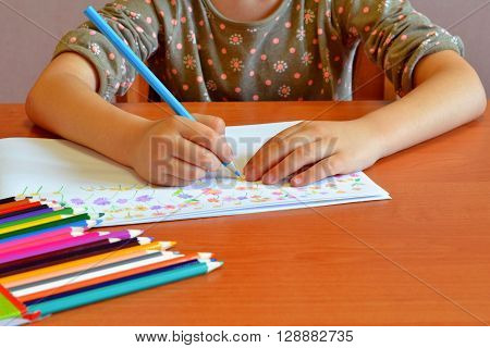 Child sits and draws flowers. Child holds a pencil in his hand. A set of colored pencils on a table. Kids drawing