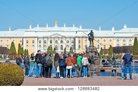 PETERHOF, SAINT-PETERSBURG, RUSSIA - MAY 8, 2016: The Upper Garden. Tourist group near The Chariot of Neptune Fountain. On the background is The Grand Palace in The State Museum Preserve Peterhof