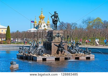 PETERHOF, SAINT-PETERSBURG, RUSSIA - MAY 8, 2016: The Upper Garden. The Neptune Fountain. On the background is The Grand Palace and The Palace Church of Saints Peter and Paul