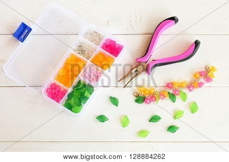 Organizer with beads, plastic flowers and accessories for handmade jewelry on white wooden background. Pliers. How to make handmade bracelet. DIY concept