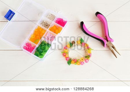 Bright beautiful handmade bracelet. Pliers. Organizer with beads, plastic flowers and accessories for handmade jewelry on white wooden background.