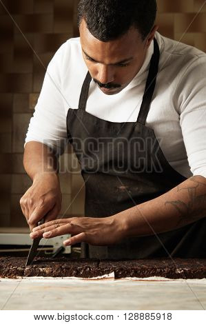 Serious Professional Black Baker Cut Piece Of Homemade Organic Chocolate With Nuts And Fruits In His