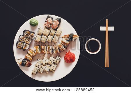 Japanese food restaurant, sushi unagi gunkan roll plate or platter set. Free, copy space, chopsticks, ginger and wasabi. Sushi at white round plate, rustic wood background. Top view with soy sauce