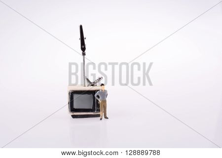 Man standing by a retro styled television set on a white background