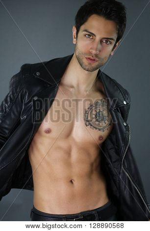 Sexy bad boy opening his leather jacket over a gray background