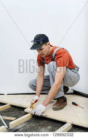 Worker measures the wooden board to cut it further.