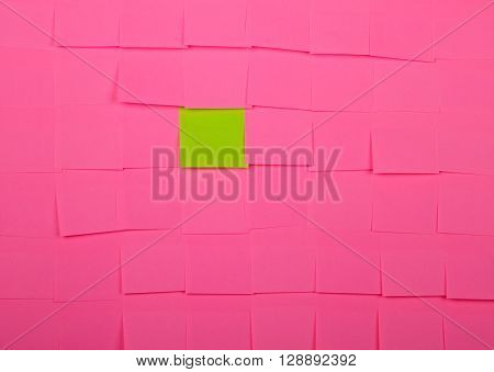 Background of a pink sticky notes. Green sticky note is among pink sticky notes.