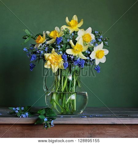 Still life with a spring bouquet with daffodils in a glass jug on a green background.