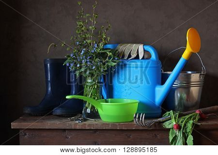 Garden still life with a spring bouquet watering can and rubber boots. Work in the garden garden tools.