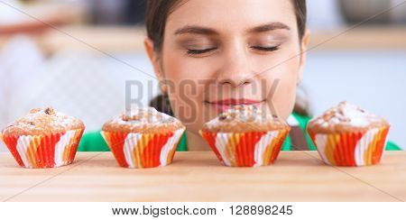 Woman is making cakes in the kitchen, looking