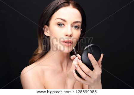 Woman performs makeup, paints lips liner pencil