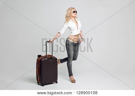 Beautiful woman tourist going on vacation, a suitcase full of things, wearing a leather jacket and gray jeans, high-heeled shoes, sunglasses