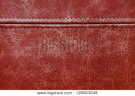 Texture red leather with seam closeup background