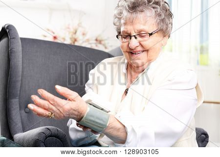 Elderly woman measures the pressure of the home sphygmomanometer wrist.