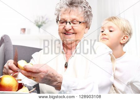 Grandmother to grandchild picks an apple peel