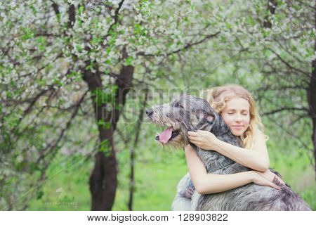 girl with the long light hair hug a huge gray wolfhound
