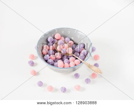 Round purple and pink bonbon candies in a bowl on white canvas background copy space