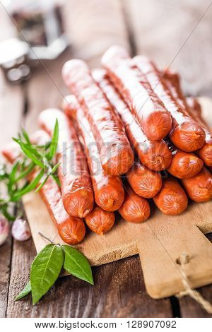 smoked sausages on wooden board on table