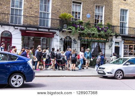LONDON UK - JUNE 6 2015 : Unidentified tourists near facade of the Sherlock Holmes house and museum in 221b Baker Street. Here is where Arthur Conan Doyle located the studio of the famous detective.