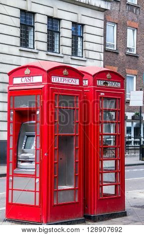 Two red phone booths on the street. One of the booths converted into ATM