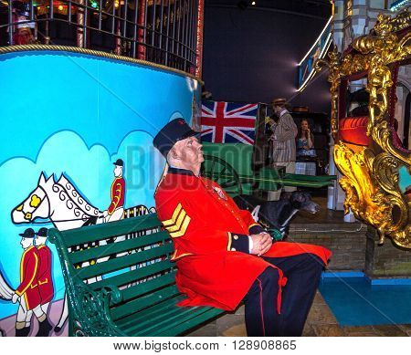 LONDON UK - JUNE 7 2015: Wax figure of Policeman in red uniform on the wooden bench at Canada Day in Madame Tussauds museum