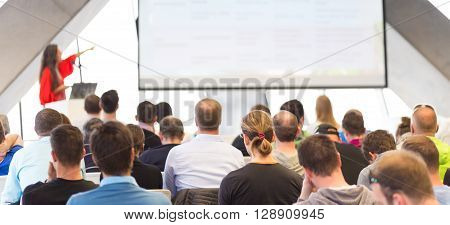 Woman giving presentation in lecture hall. Male speeker having talk at public event. Participants listening to lecture. Rear view, focus on people in audience.