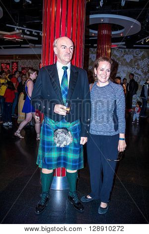LONDON UK - JUNE 7 2015: Unidentified girl makes photo for memory with Sean Connery wax figure in Madame Tussauds museum in London. Marie Tussaud was born as Marie Grosholtz in 1761