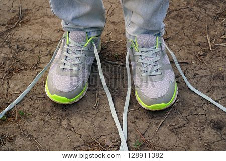 young girl commits an outdoor walk and stopped to tie his shoelaces on sneakers.